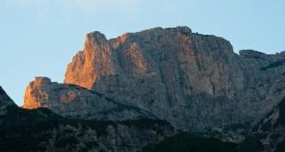 Zahajajoče sonce osvetljuje zahodni rob hriba